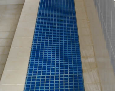 Using blue FRP gratings with square holes as trench covers.