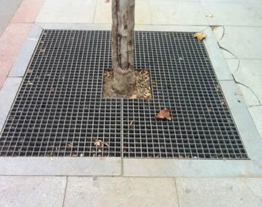 A piece of dark grey FRP grating is covering the ground around the root of a tree.