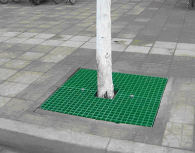 The ground around a tree is covered by a piece of green FRP grating with square holes.