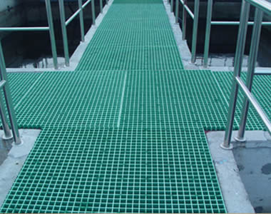 Green FRP gratings with square holes are spread upon the surface of walkways.