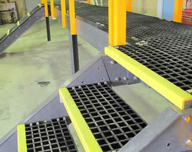 Black FRP grating panels together with yellow stair nosing act as stair treads.