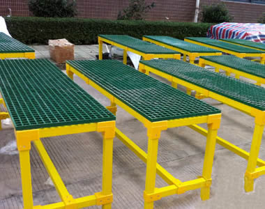 Several shelves made of yellow FRP frames and green FRP grating panels are standing on the ground.