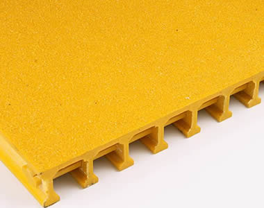A piece of yellow pultruded FRP grating with gritted top covered surface.
