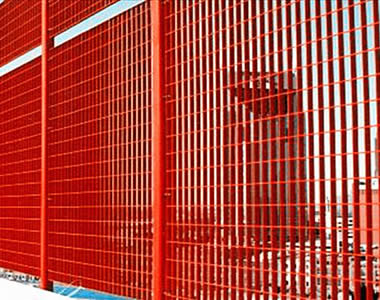 Red FRP grating safety fences with added height and red posts stand on the ground.