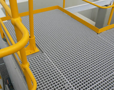 Grey molded FRP gratings with square holes act as the surface of a operating platform, which has yellow fences.