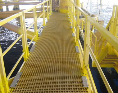 The walkway of a offshore oil platform is made of yellow FRP gratings with square holes.