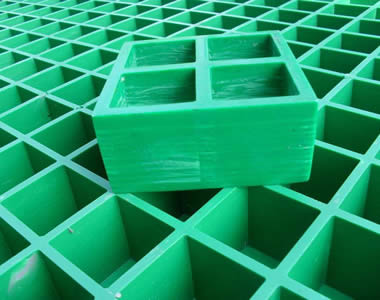 A small green FRP grating on another big green FRP grating, and they both have polished smooth surface and square holes.