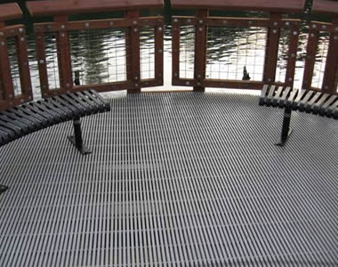 Grey pultruded FRP gratings as the floor over a lake.