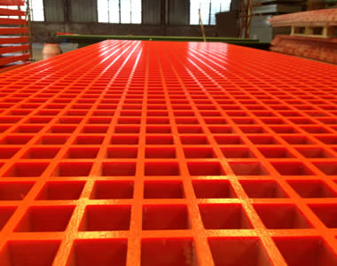 A large piece of red molded FRP gratings with square holes is expanding on the ground.