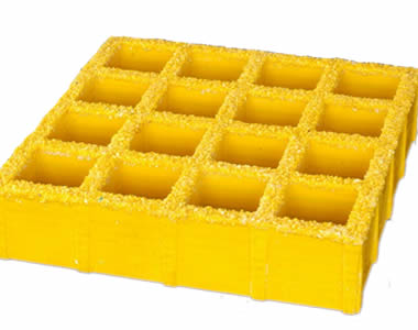 A piece of yellow molded FRP grating with sanding surface and sixteen square holes.