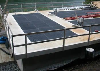 A waste water platform made of concrete frame and black FRP gratings, and the platform is near a lake.