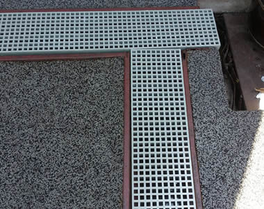 The trenches are covered by white FRP gratings with square holes.