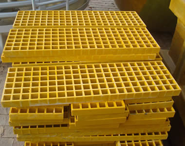 A stack of yellow FRP gratings with smooth surface and square holes.