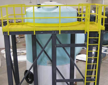 The top of a tank is surrounded by yellow FRP gratings, and there are fences and a ladder on it.