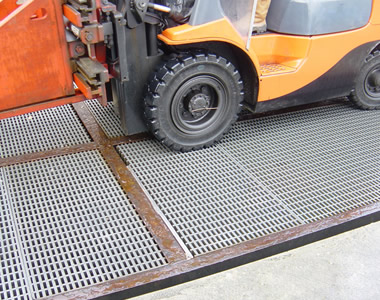 There is a forklift on the high load capacity grating.