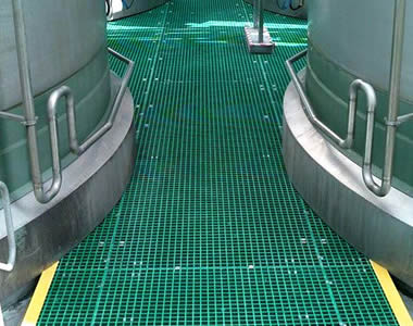 There are green FRP grating ways between two columns of big equipment.