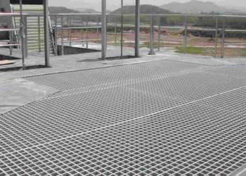Several pieces of grey FRP gratings make up a large FRP floor over the concrete ground.