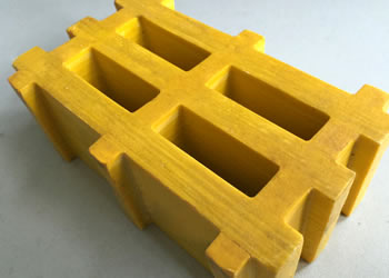 There is a piece of yellow high load capacity grating with four meshes.
