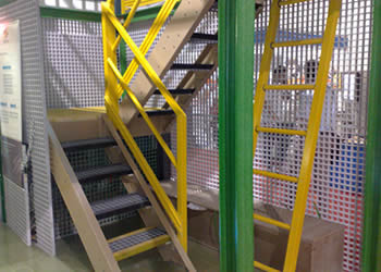 There are grey FRP stair panels, black  FRP stair nosing, green FRP posts, yellow FRP fences and ladders in the FRP stair system.