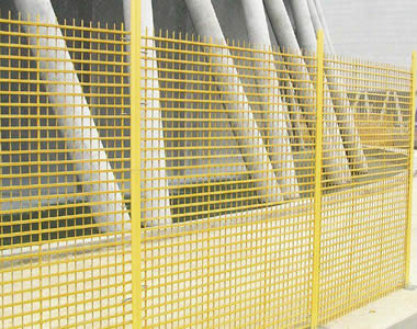 Several pieces of yellow FRP grating panels make up a FRP fences together with several yellow FRP posts.