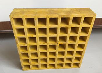 There is a piece of square yellow heavy load capacity grating with 49 meshes standing on the ground.