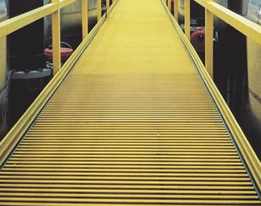 Yellow pultruded FRP gratings are acting as the gangway of a factory, and there are yellow FRP fences alongside.